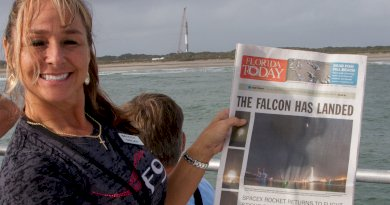Karen LaFon holds the Falcon has Landed headline in front of the Falcon 9 that landed in Florida. Photo: Bill Jelen