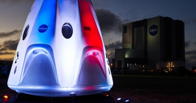 A mockup Crew Dragon at Kennedy Space Center is lit up in red, white and blue prior to the launch of SpaceX's first operational crew rotation mission.  Photo credit: Jared Haworth / We Report Space
