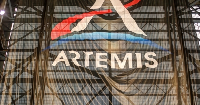 A large Artemis mission flag hangs inside NASA's Vehicle Assembly Building.  Photo credit: Michael Howard / We Report Space